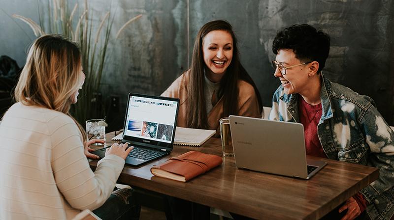 Tre ungdomar sitter vid ett bord och skrattar. Två datorer står på bordet. Bredvid en dator ligger ett anteckningsblock.