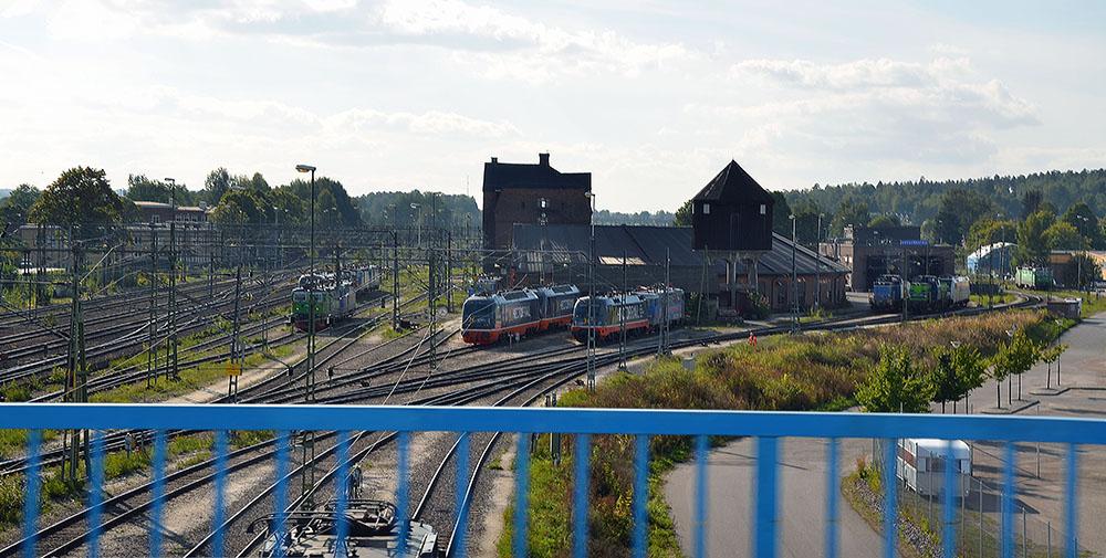 Viaduktens blå staket i förgrunden. Bakom syns järnvägsspåren och tågset på rangerbangården.