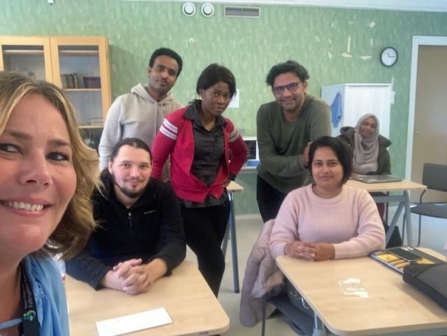 En selfi på Jenny Molin med kursdeltagarna längre bak i klassrummet.