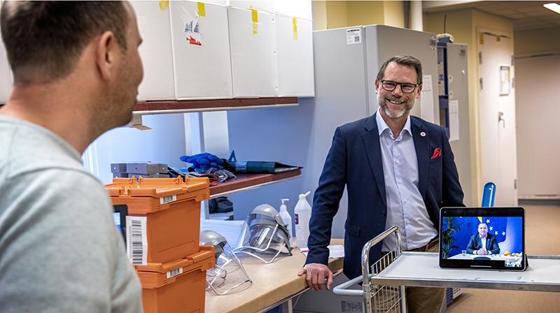 Erik Fredholm och Andreas Svahn står och pratar mitt emot varandra. Stefan Löfven finns med på bilden via en länk på en dator.